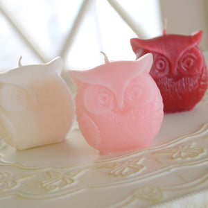 three owl candles in the colors, red, pink and white
