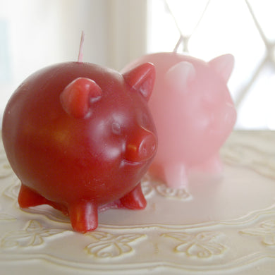 set of two pig candles red and pink scented in black raspberry vanilla