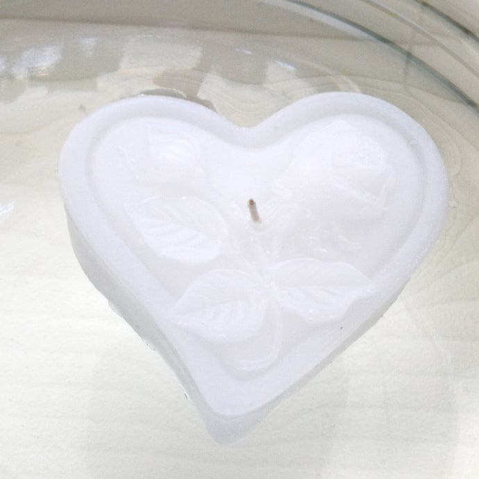 white heart shaped floating candles with rose motif for wedding reception centerpieces