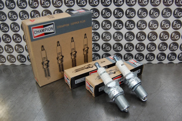 Photo of a pair of Champion N5C spark plugs used in vintage Triumph motorcycles with Franz and Grubb logo in background