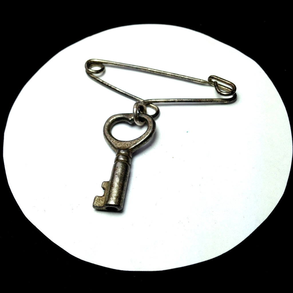 TEASDALE Sterling safety pin with antique heart-shaped key pendant/Front.