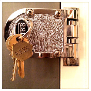 "Hand stamped brass keyring ""KEYS"", on door"