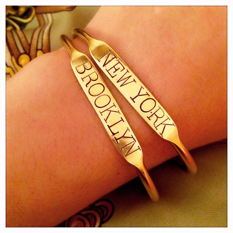 "Hand stamped brass cuff ""Brooklyn"" on wrist with NY cuff"