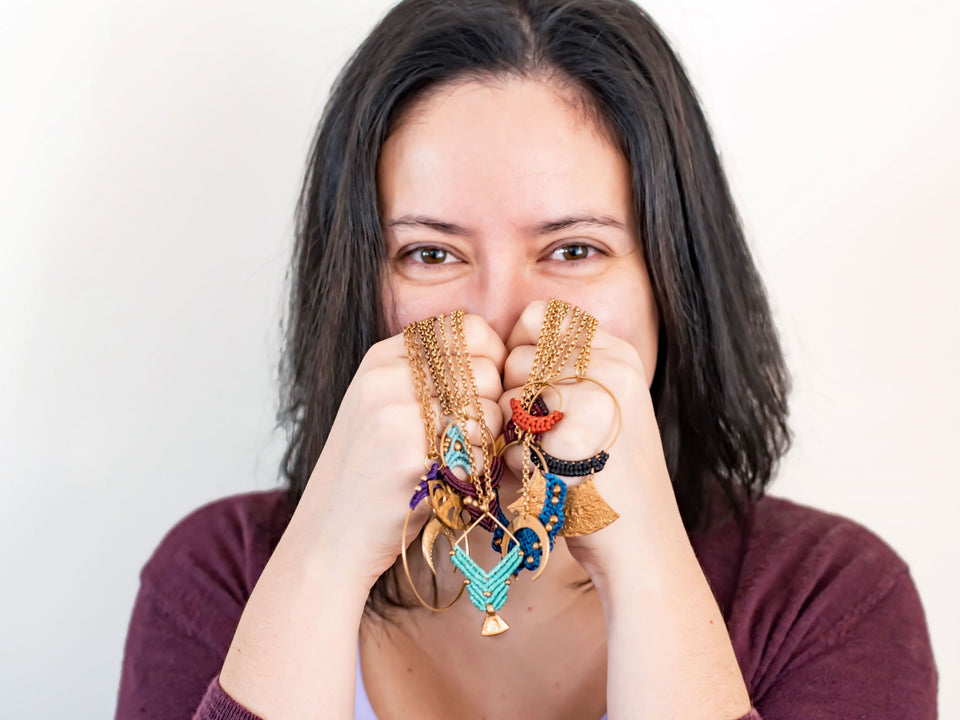 Designer holding necklaces made from macrame and brass