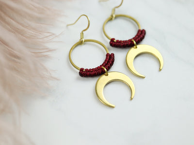Sideview of moon style drop macrame earrings in dark red and gold color with grey background.