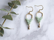 Load image into Gallery viewer, Hexagon shaped drop macrame earrings in green and golden color with white background.