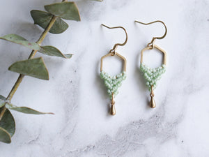 Hexagon shaped drop macrame earrings in green and golden color with white background.