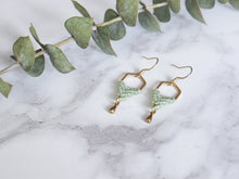 Load image into Gallery viewer, Side View of Hexagon style drop macrame earrings in green and golden color in white background.