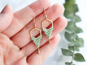 Hands showing Hexagon style drop macrame earrings in green and golden color.