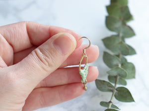 Hands showing single Hexagon style drop macrame earrings in green and golden color.