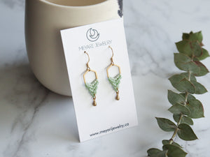 Paie of Hexagon style drop macrame earrings in green and golden color in white background.