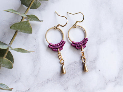 Closeup of Simple drop macrame earrings in purple color with white background.