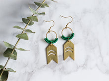 Load image into Gallery viewer, Pair of Arrow drop macrame earrings made from brass with white background.