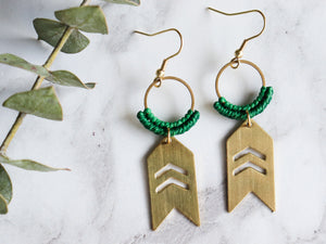 Close up of pair of Arrow drop macrame earrings made from brass with white background.