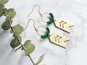 Pair of Arrow drop macrame earrings made from brass with white background.