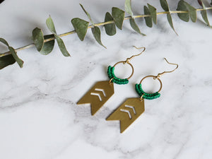 Top view of Pair of Arrow drop macrame earrings made from brass with white background.