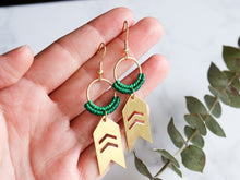 Load image into Gallery viewer, Closeup of Arrow drop macrame earrings made from brass with green leaves on right side.