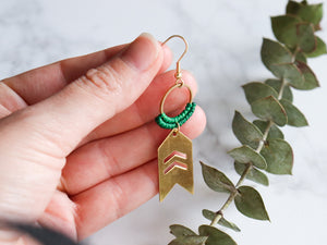 Fingers holding single Arrow drop macrame earrings made from brass.