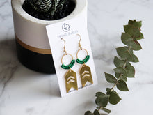 Load image into Gallery viewer, Arrow drop macrame earrings made from brass with green leaves on right side.