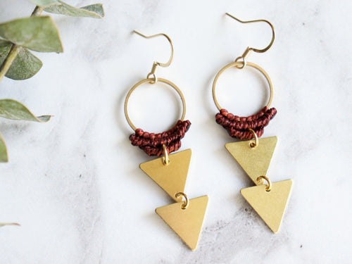 Pair of Double triangle drop macrame earrings in red and golden color in white background.
