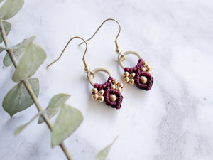 Closeup Pair of wine color Arya macrame earrings made from raw brass.