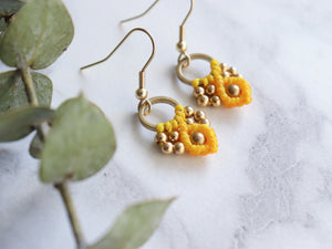Closeup Pair of yellow color Arya macrame earrings made from raw brass.