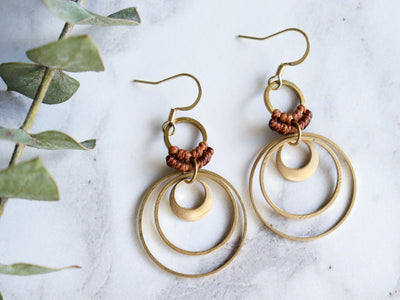 Pair of Multiple circle drop style macrame earrings in brown and golden color.
