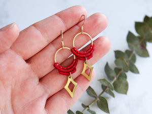 Hand holding Red Hollow diamond style drop macrame earrings.