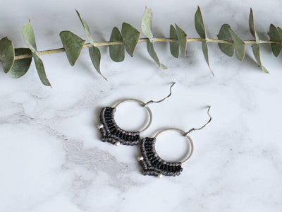 Pair of black color silver two tone macrame earrings in white background.