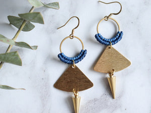 Closeup of Pair of Handmade Brushed triangle with spike macrame earrings in golden and blue color.