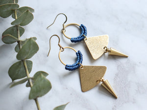 Sideview of Pair of Handmade Brushed triangle with spike macrame earrings in golden and blue color.