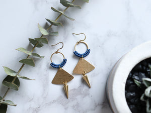 Top view of Pair of Handmade Brushed triangle with spike macrame earrings in golden and blue color.