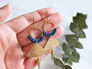 Hands holding Pair of Handmade Brushed triangle with spike macrame earrings in golden and blue color.