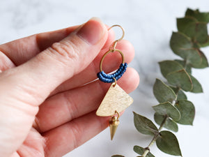 Hands holding single Handmade Brushed triangle with spike macrame earrings in golden and blue color.