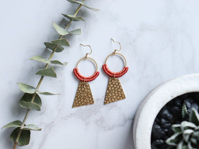 Pair of Red & Golden Textured quadrilateral macrame earrings in white background.