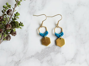 Closeup Mini hexagon style macrame earrings in blue and golden color.