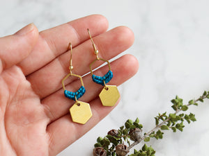 Hands holding Mini hexagon style macrame earrings in blue and golden color.