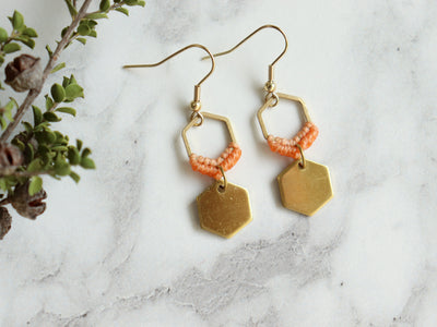 Closeup Mini hexagon style macrame earrings in orange and golden color.