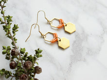 Load image into Gallery viewer, Side view of Mini hexagon style macrame earrings in orange and golden color.