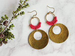 Closeup of Hammered circle Style drop macrame earrings in pink and golden color Made with knotted waxed polyester and brass.