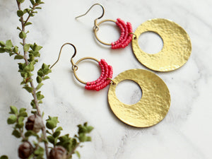 Sideview of Hammered circle Style drop macrame earrings in pink and golden color Made with knotted waxed polyester and brass.
