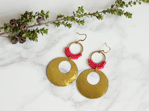 Topview of Hammered circle Style drop macrame earrings in pink and golden color Made with knotted waxed polyester and brass.