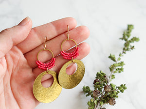 Hands holding Hammered circle Style drop macrame earrings in pink and golden color Made with knotted waxed polyester and brass.