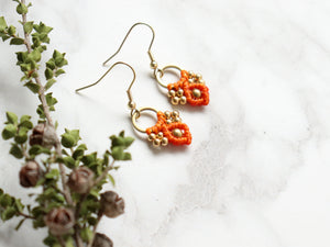Closeup Pair of orange color Arya macrame earrings made from raw brass.