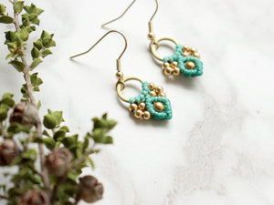 Closeup Pair of green color Arya macrame earrings made from raw brass.