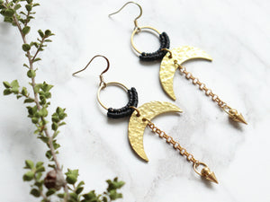 Sideview of Pair of Hammered style drop macrame earrings in gold and black color.