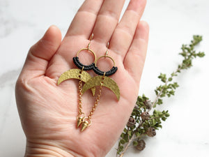 Pair of Hammered style drop macrame earrings in gold and black color in hands.