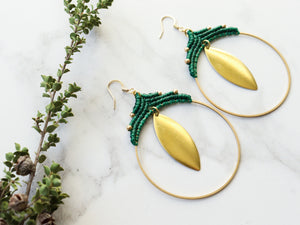 Pair Big leaf hoop macrame earrings in gold and green color with white background.