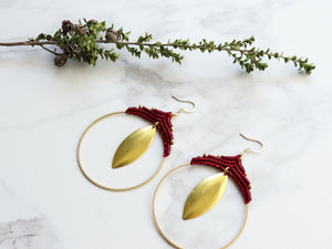 Side View of Pair Big leaf hoop macrame earrings in gold and red color with white background.
