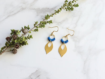 Mehndi Leaf style Drop Earrings in blue and golden color with white background.